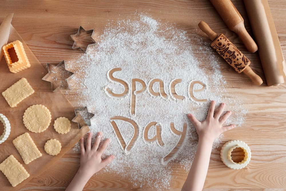 Space Day concept using homemade cookies and flour set on a wooden table.