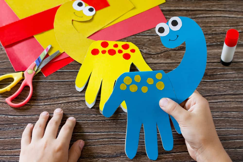Kid holding a blue paper plate dinosaur that he created on the wooden table.