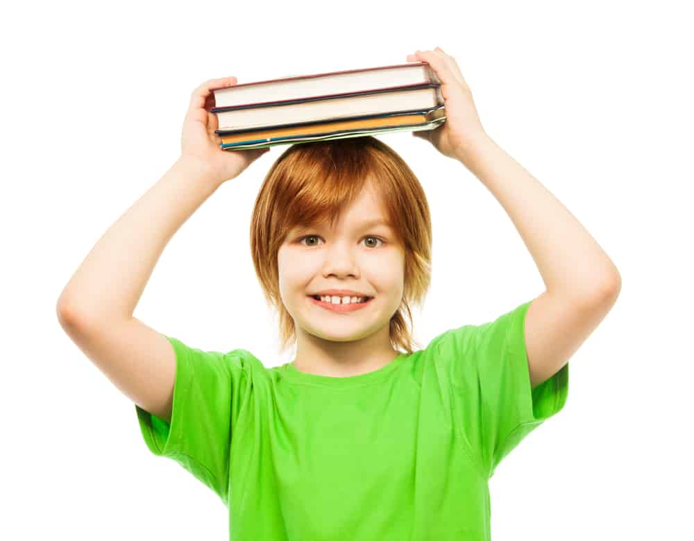 An eight-year-old boy in a green shirt carrying books over his head.