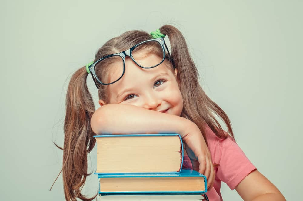 A five-year-old girl with glasses leans on a stack of books.