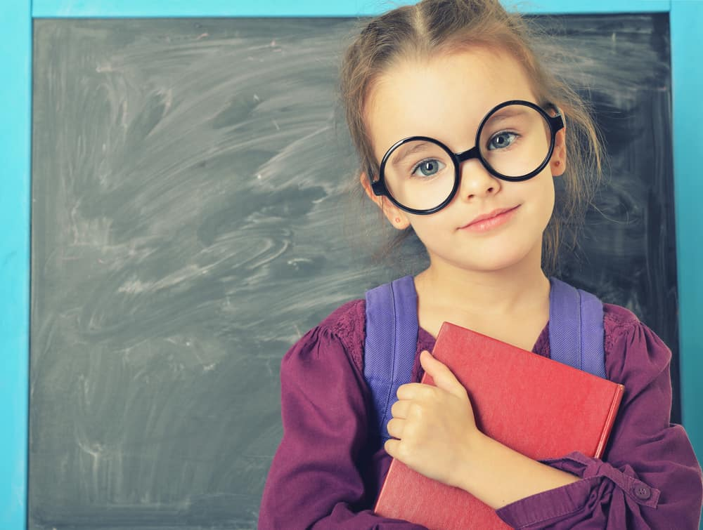 A six-year-old girl with glasses holding a book in front of a blackboard.